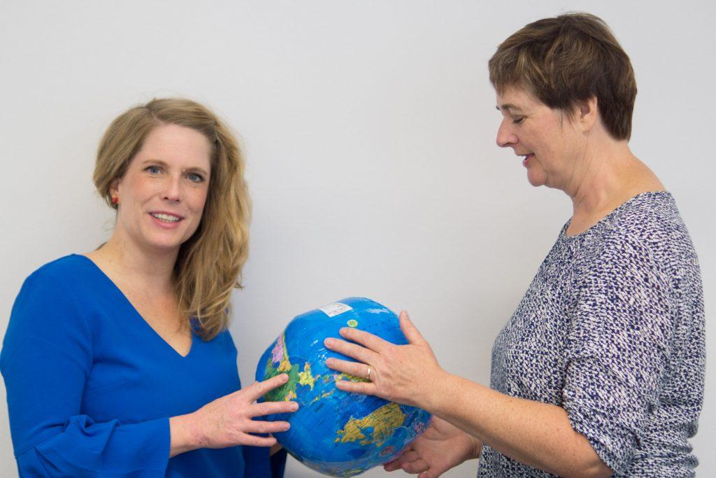 Joanna Egger und Eva Fleischer halten einen Globus in der Hand.